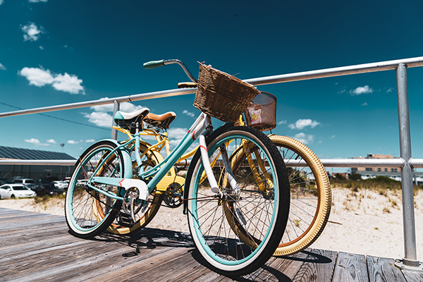 Seaside Park rental beach cruiser bikes in teal and pale yellow with baskets parked on boardwalk